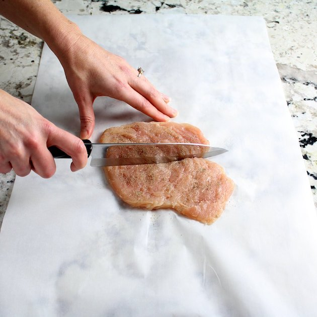 Cutting uncooked chicken breast in half