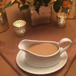 white wine turkey gravy in gravy boat on Thanksgiving dinner table