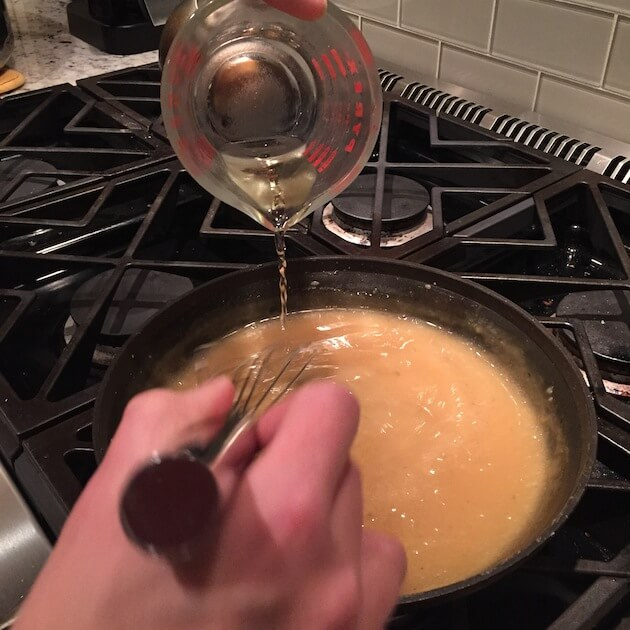 adding white wine into saucepan for turkey gravy