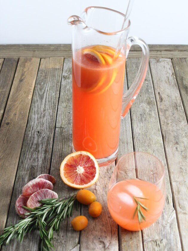 Tall glass pitcher with orange colored punch and fruit
