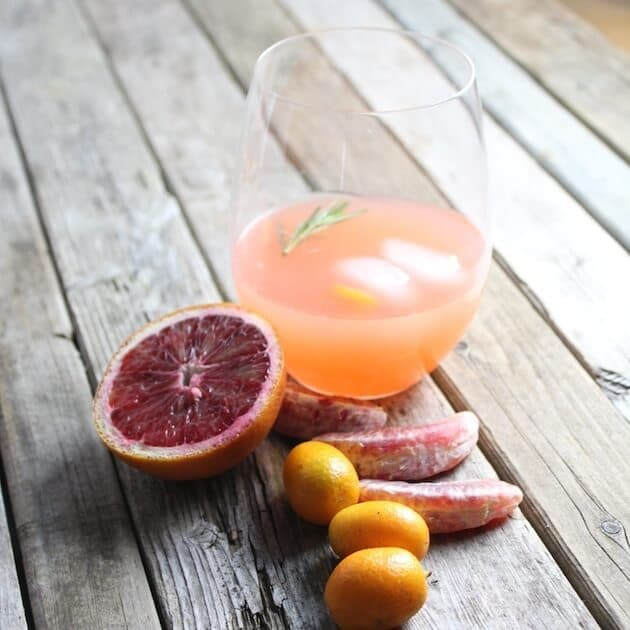 Aperol Punch glass on farm table with citrus garnishes