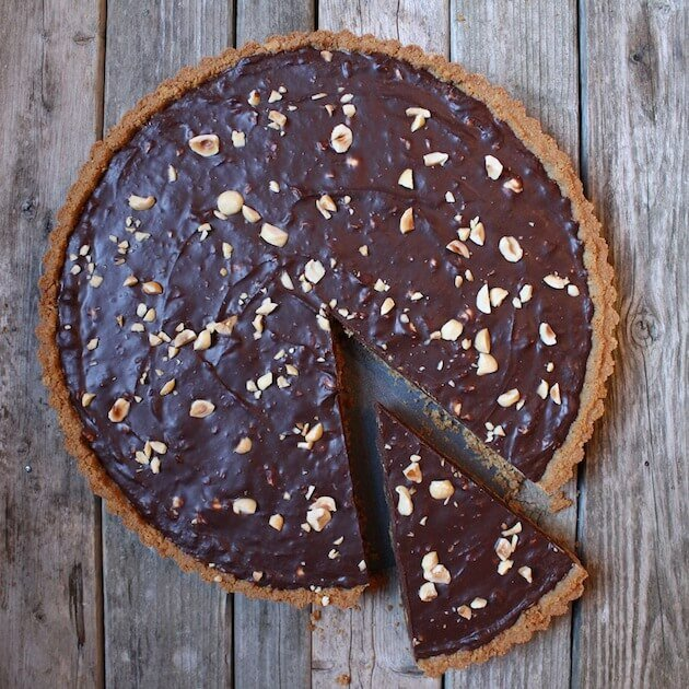Chocolate Hazelnut Tart on farm table with slice partially removed