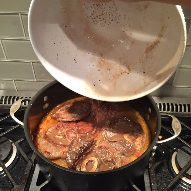 Veal Osso Buco Pan juices pouring into Dutch Oven