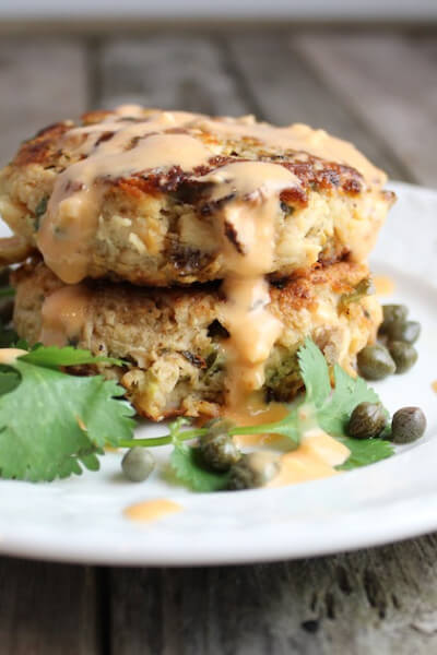 Tuna cakes stacked on a plate with aioli sauce
