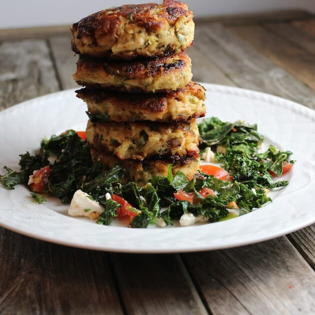 5 Tuna Cakes stacked on a plate, with kale feta salad