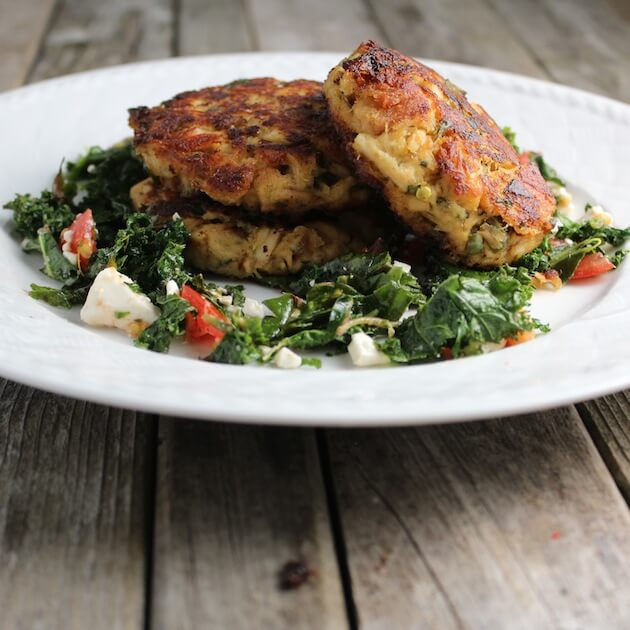 Three Tuna Cakes patties stacked on a plate with kale feta salad