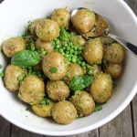Potato salad with peas and potatoes in white serving bowl