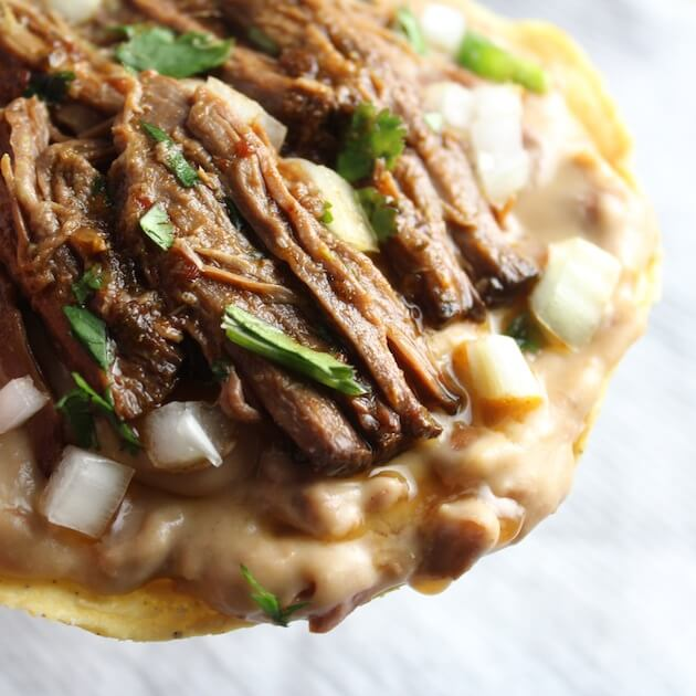 Beef Barbacoa on refried beans