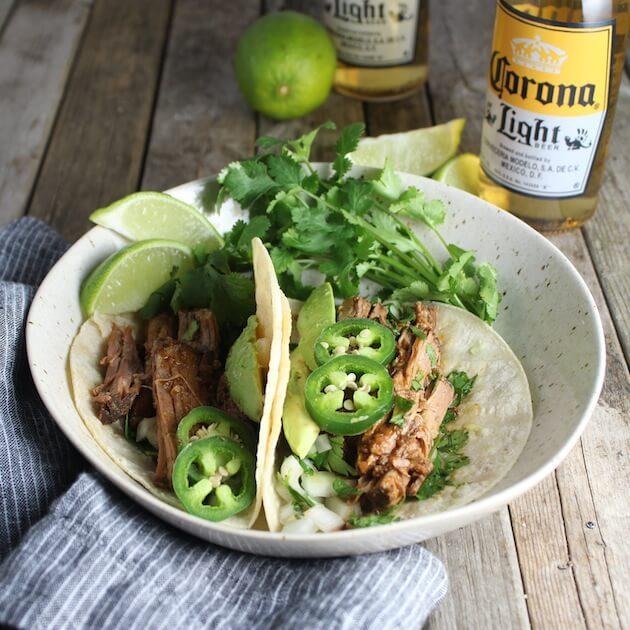 Slow Cooker Beef Barbacoa taco and corona beer in background