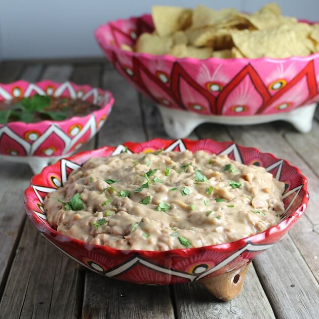 Mexican Pattern Bowls with Chips, Salsa, and homemade refried beans on a farm table