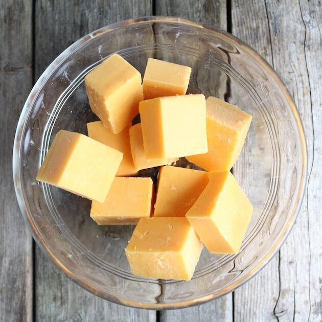 Cubes of cheddar cheese in a small glass bowl
