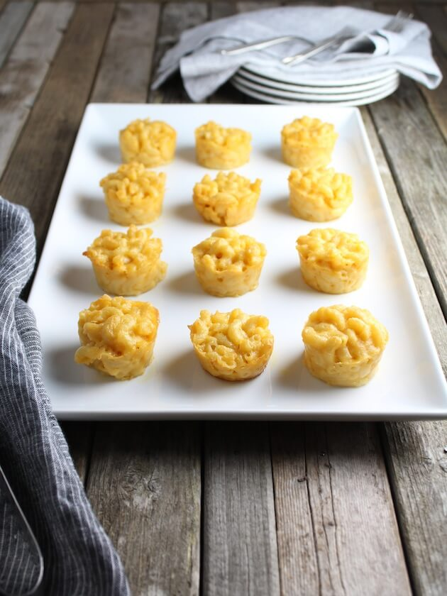 Macaroni and Cheese mini appetizers on farm table with stack of plates
