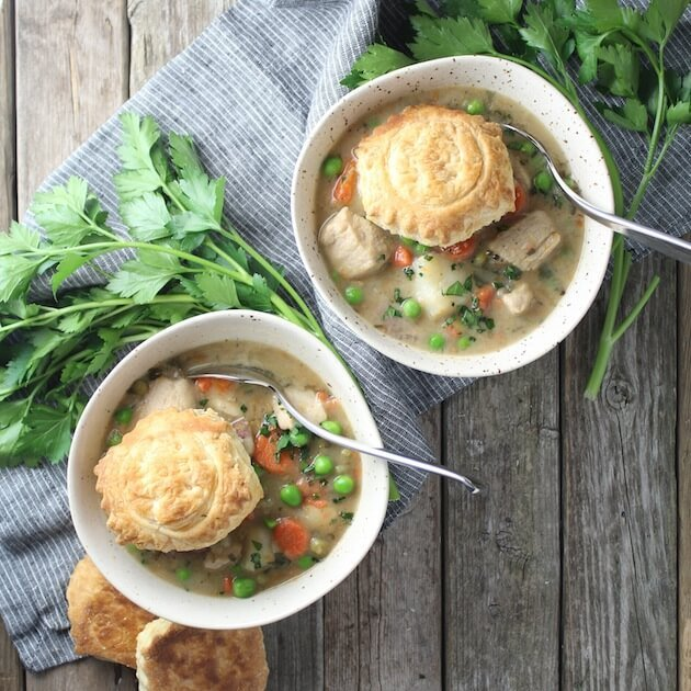 Two bowls of Chicken Pot Pie Soup on farm table with parsley and puff pastry shells
