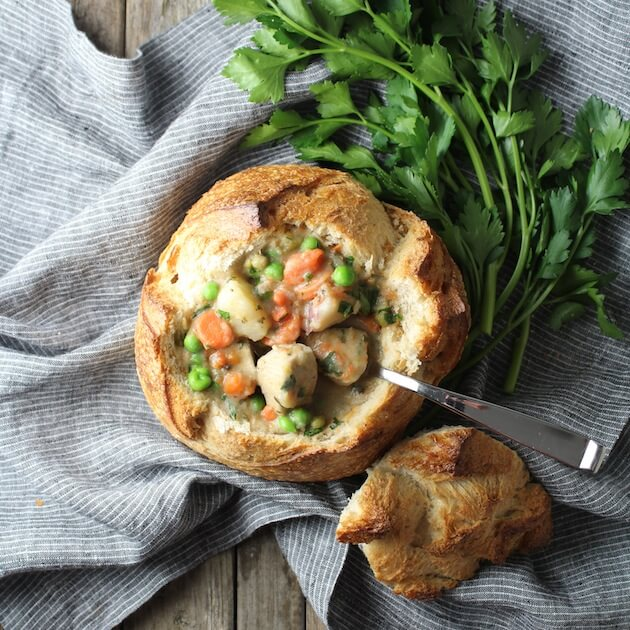 Chicken Pot Pie Soup in a bread bowl on farm table