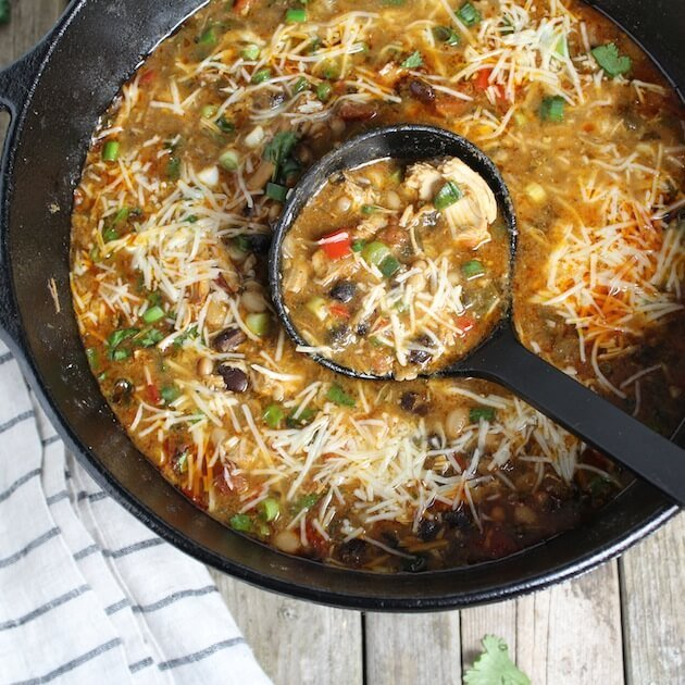 Smoky Chicken Chili in soup pot with shredded cheese