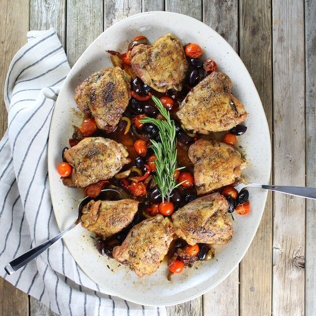 Chicken Fricassee thighs on platter with tomatoes, olives, peppers