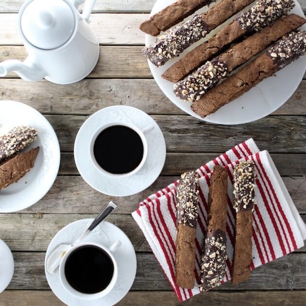 Table with multiple Chocolate Coffee Hazelnut Biscotti and cups of coffee
