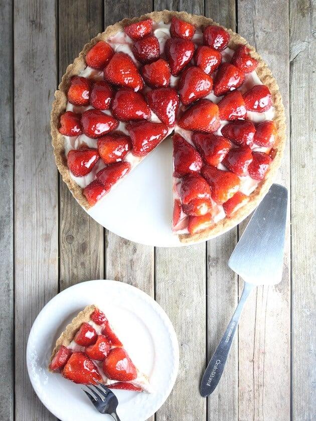 Slice of tart on a plate next to Strawberry Mascarpone on cake platter