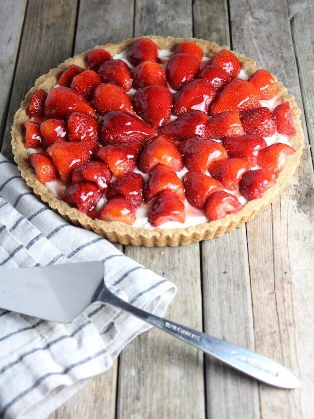 Strawberry Mascarpone Tart on farm table with spatula