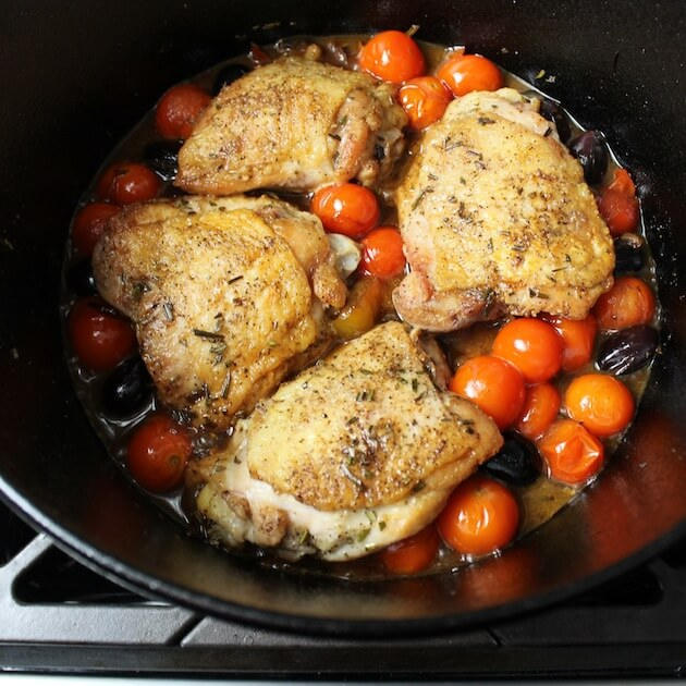 Chicken thighs in cast iron pot with tomatoes and kalamata olives