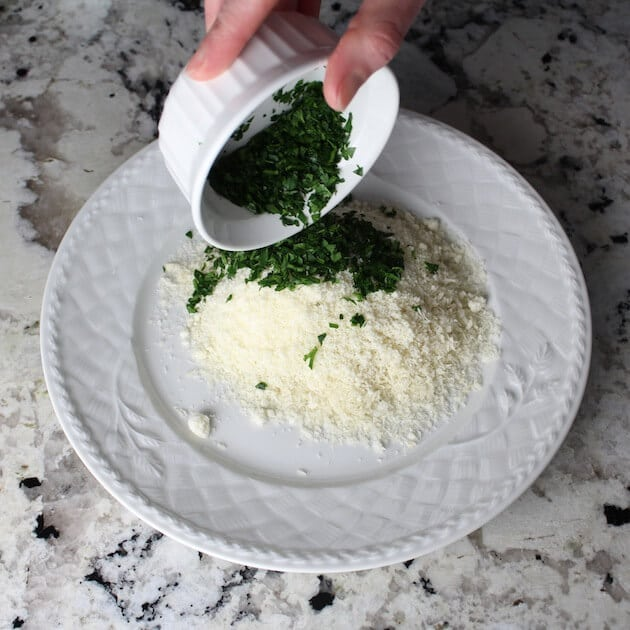 Adding chopped parsley to plate of grated Parmesan cheese