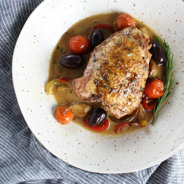 Seared and braised chicken thigh in bowl with tomatoes, peppers, and kalamata olives (chicken fricasee)