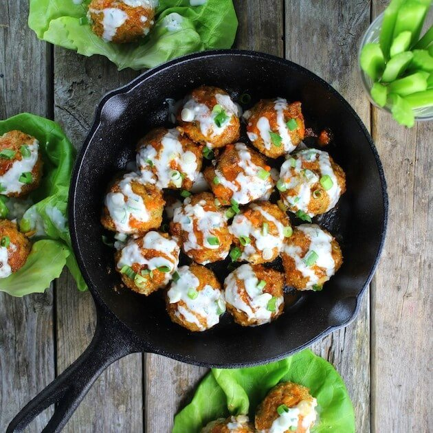 Cast Iron skillet full of Buffalo Chicken Meatballs covered in Blue Cheese Sauce