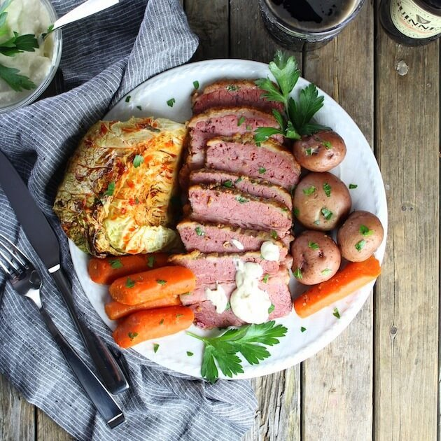 Full St. Patricks day Corned Beef And Cabbage meal on a plate with silverware and napkin
