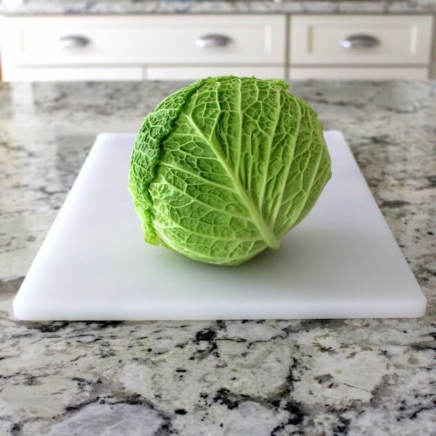 Beautiful bright green whole cabbage on cutting board in kitchen