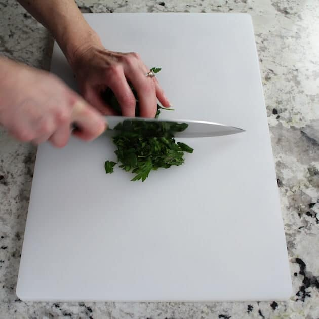 chopping parsley on cutting board