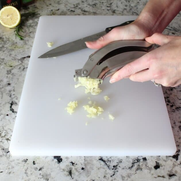 Mincing garlic onto cutting board