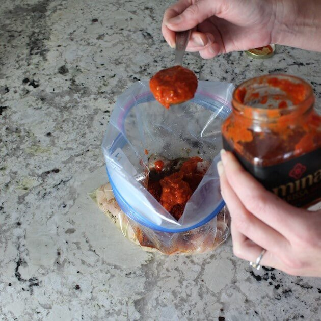 Adding Harissa sauce to resealable bag for marinating chicken