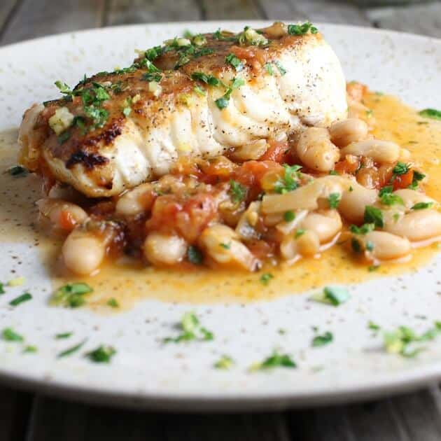 Pan Seared Halibut With White Beans And Gremolata on a plate