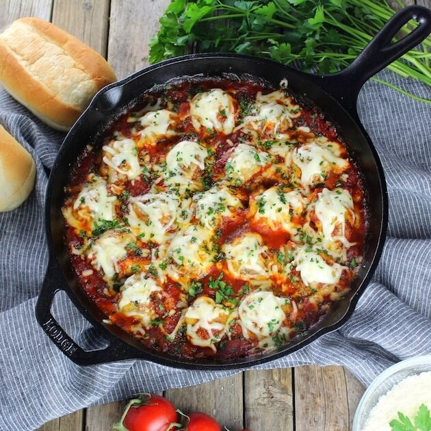 Skillet full of Italian meatballs in red sauce covered with cheese