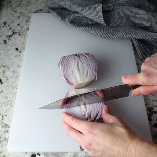 Cutting red onion on cutting board