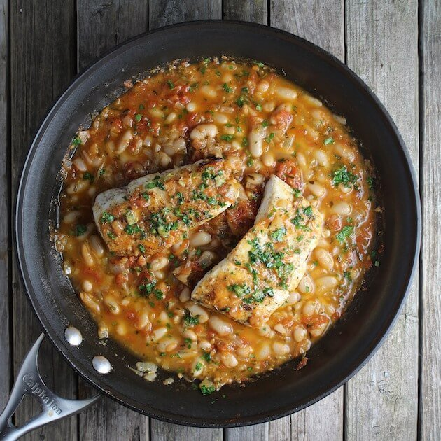 Saute Pan with two filets of Seared Halibut over White Beans with Gremolata