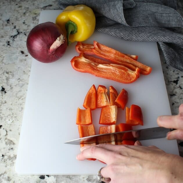 Cutting red peppers on cutting board