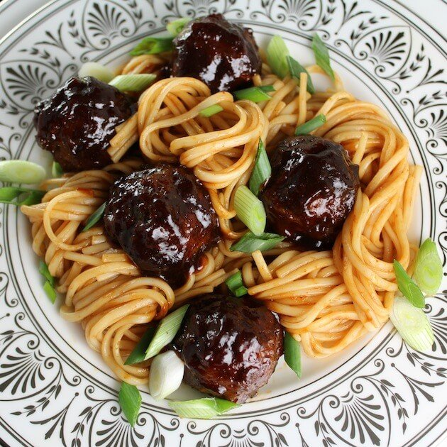 Asian Meatballs on decorative plate with noodles and chopped green onions