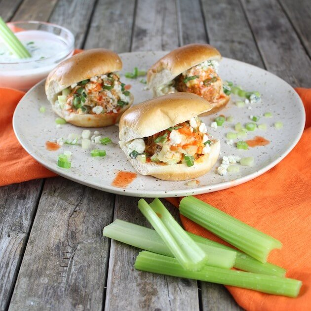 Three Buffalo Chicken Meatball sliders nice on a plate with celery sticks