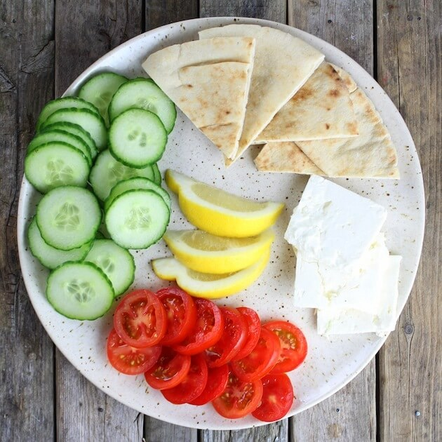 Platter of cucumbers, tomatoes, feta cheese, lemons and pitas for a Greek meal