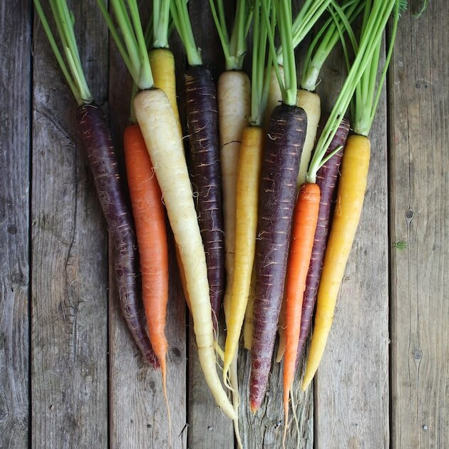 Fresh Rainbow Carrots with stalks on farm table
