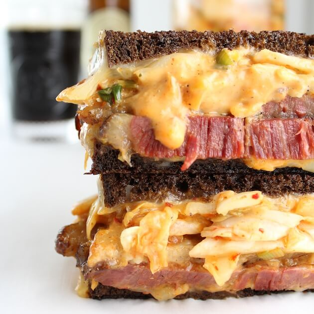Close up of mouthwatering reuben sandwich oozing with thousand island and kimchi on pumpernickel