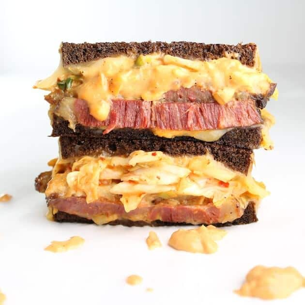 Two stacked halves of kimchi reuben sandwich thick corned beef on pumpernickel bread