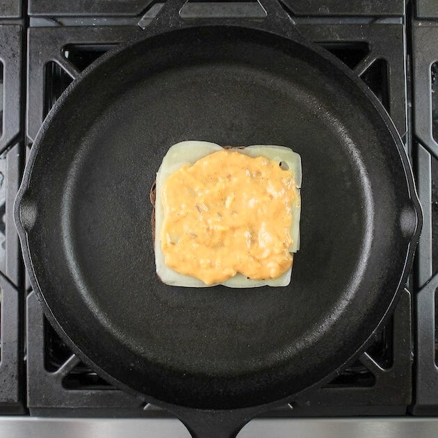 Adding layers of swiss cheese and thousand island to reuben sandwich in cast iron skillet