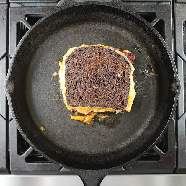 Toasting the kimchi reuben sandwich in cast iron skillet