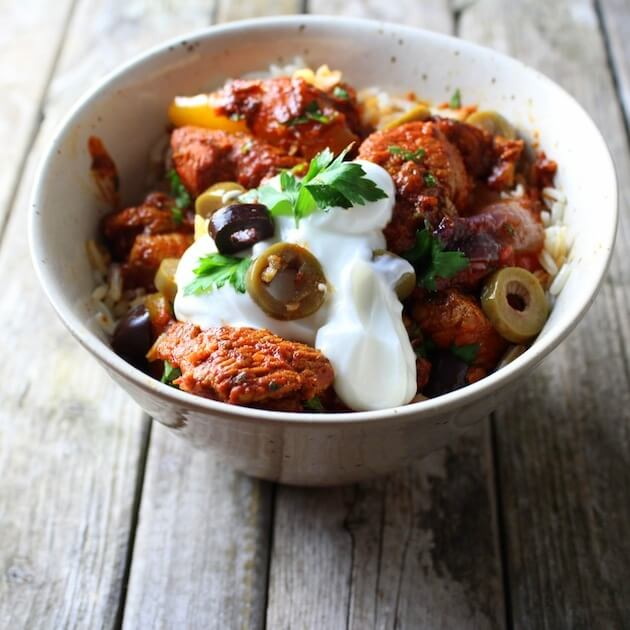 Bowl of spicy chicken topped with yogurt and olives