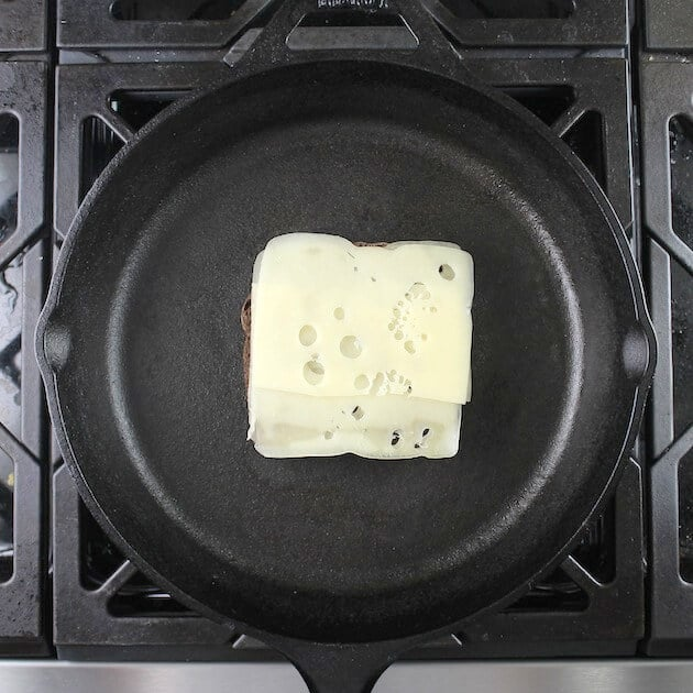 Adding swiss cheese to pumpernickel bread in cast iron skillet