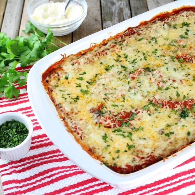 Partial casserole dish with cooked Lasagna topped with melted cheese and parsley