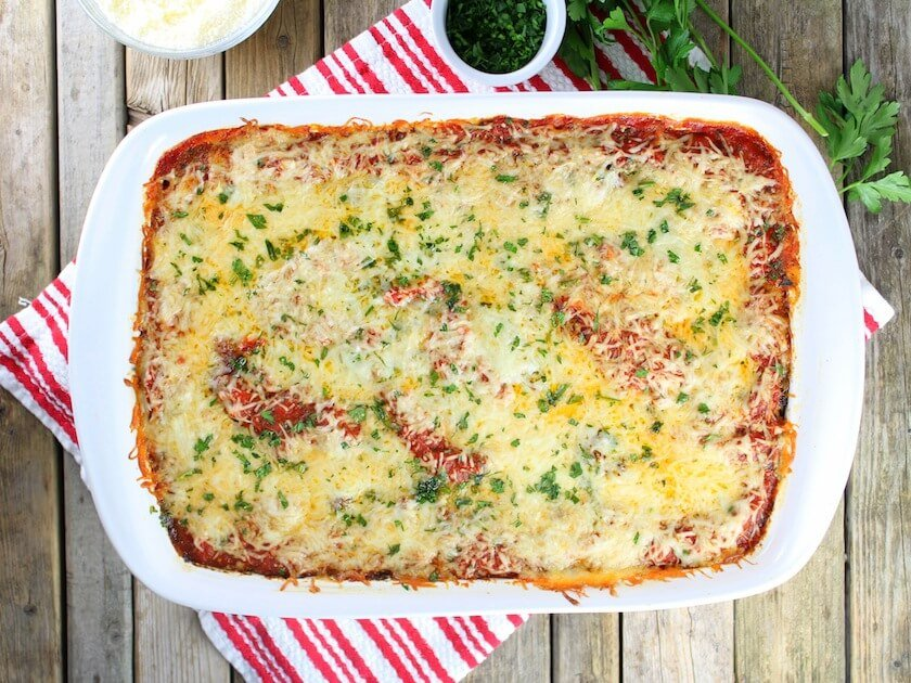Lamb Lasagna With Parmesan Polenta in white casserole dish on farm table