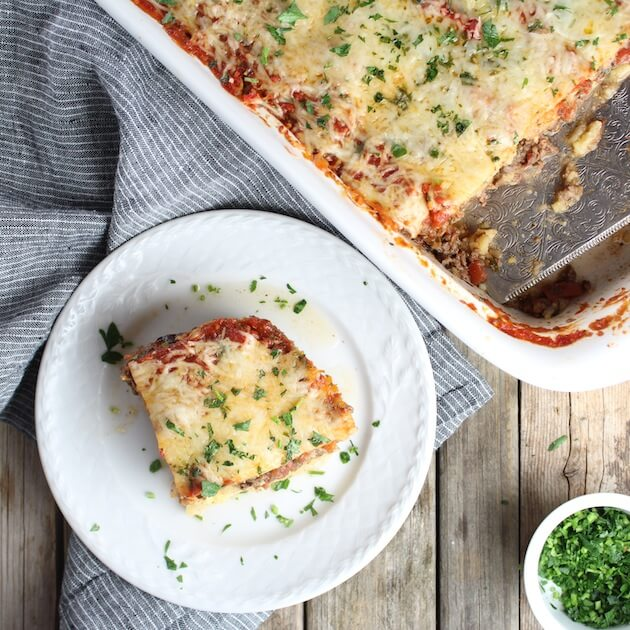 Piece of Lamb Lasagna on a plate next to full casserole dish